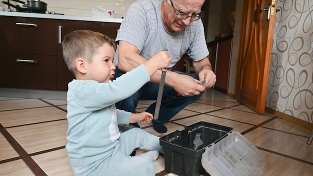 Little boy plays with grandpa , show tools at home. family relationships between grandfather and grandson. learning concept.