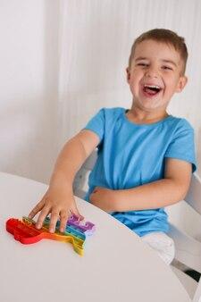 小さな男の子はレインボーポップイットフィジェットおもちゃで遊ぶ。アンチストレスチルドレンゲーム。子供のトレンディなシリコーンのおもちゃは、ストレスを和らげ、手の運動能力を発達させるためにそれをポップします。プッシュバブルとカラフルな手のおもちゃ。