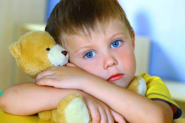 Little boy plays with a teddy bear
