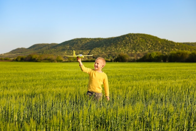 A little boy plays with a yellow toy plane on a green wheat field.