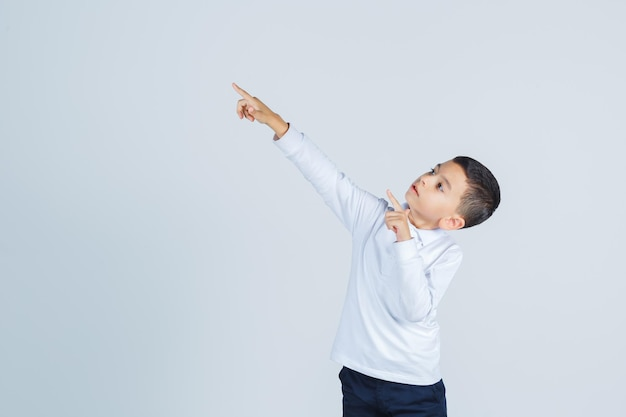 Little boy pointing at upper left corner in white shirt, pants and looking confident. front view.