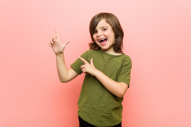 Little boy pointing with forefingers to a copy space, expressing excitement and desire