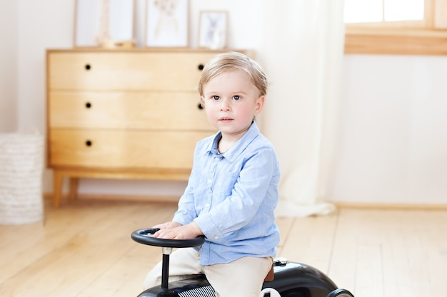 Little boy. portrait child riding toy vintage car. funny kid playing at home. travel concept. active little boy driving a car pedal in the nursery. toddler driving a retro car, boy in toy car