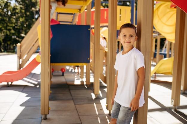 小さな男の子が遊び場でポーズをとって、幸せな子供時代。子供はトランポリンで遊ぶ
