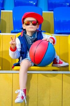 Маленький мальчик позирует на баскетбольной площадке.