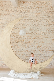 Little boy posing on big moon toy with loft brick wall background