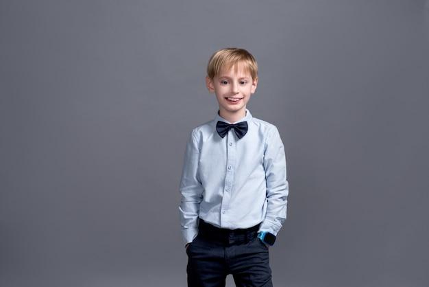 Little boy posing on grey