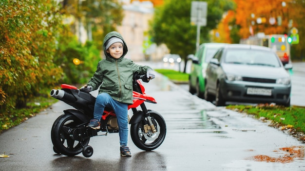 A little boy posing at his children's red motorcycle.