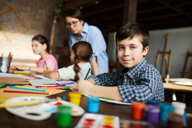 Маленький мальчик позирует в художественном классе