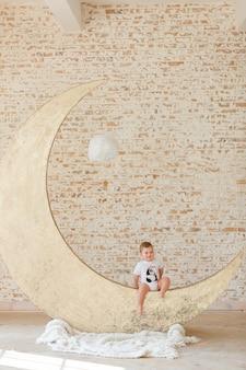 Маленький мальчик позирует на большой лунной игрушке с чердаком кирпичной стены фон