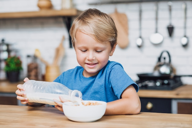 Little boy pouring milk in bowl of cereal