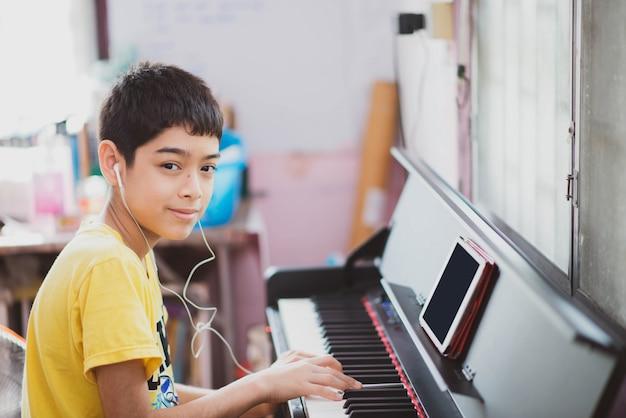 Маленький мальчик практикующих фортепиано онлайн цифровой планшет на дому
