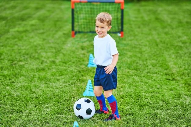 야외에서 축구를 연습하는 어린 소년