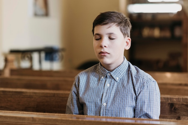 그의 눈을 감고 교회에서기도하는 어린 소년