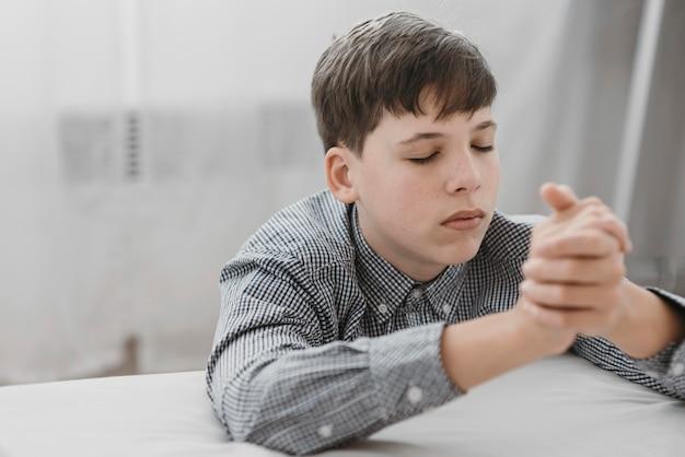 Маленький мальчик молится на коленях дома