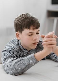 Маленький мальчик молится на коленях