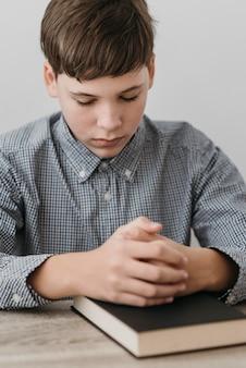 Маленький мальчик молится, положив руки на библию