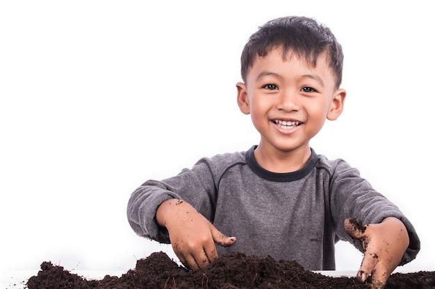 Little boy preparing the soil for planting