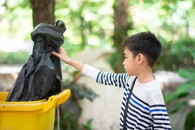 Little boy put the black garbage bag into the trash