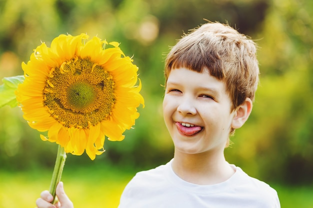 Little boy put out his tongue and holding sunflower.