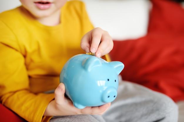 Little boy putting coin into piggy bank