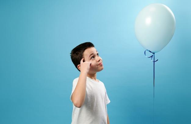 Маленький мальчик, положив палец на висок и задумчиво глядя на летающий синий воздушный шар