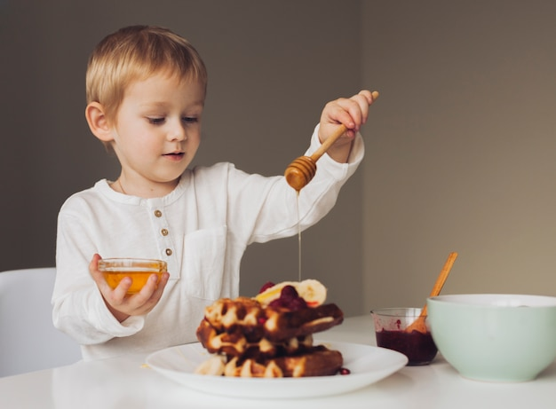 Little boy putting honey on waffle