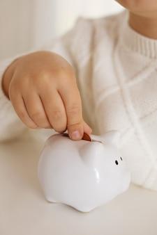 お金を節約するために貯金箱にお金のコインを入れる小さな男の子。富、予算、投資、財務の概念。子供と貯金箱、貯金箱。