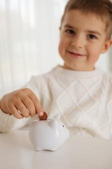 Little boy putting money coin into piggy bank for saving money. wealth, budget, investment, finance concept. child and money box, piggybank.