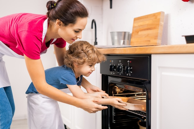 Little boy putting tray into open oven and his mom helping him after making homemade cookies on weekend