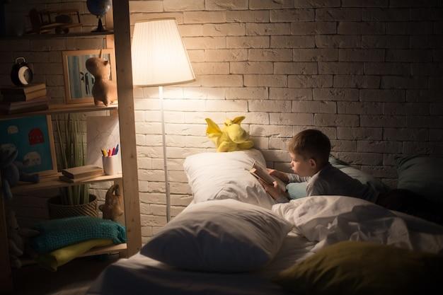 Маленький мальчик читает книгу ночью