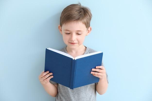 색상 표면에 책을 읽는 어린 소년