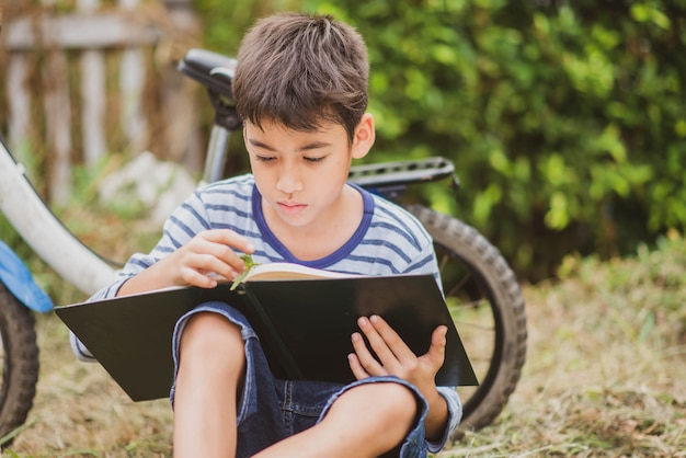 Little boy reading book sitting with bicycle in the park