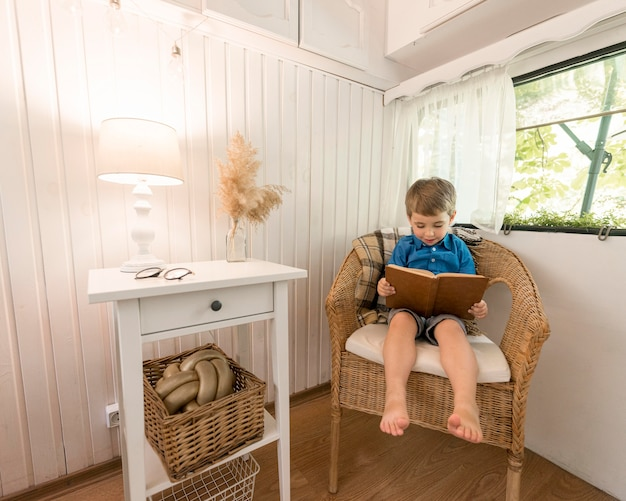 Little boy reading a book while sitting on an armchair