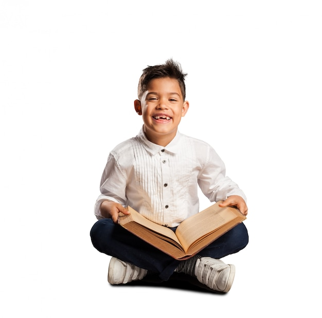 Little boy reading a book on white background