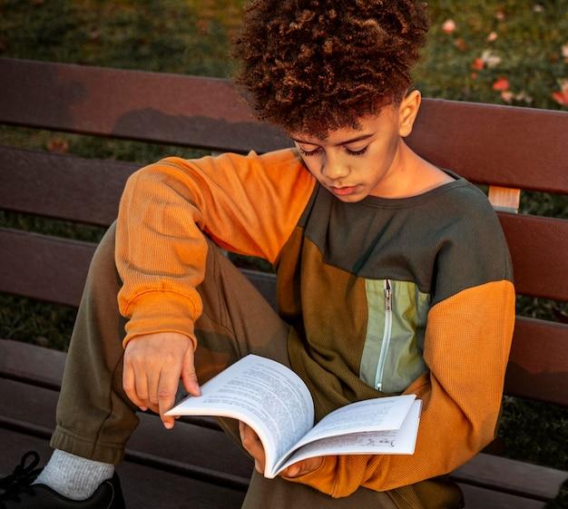 Маленький мальчик читает на скамейке