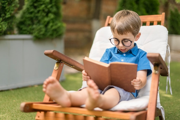 Little boy reading while sitting outside