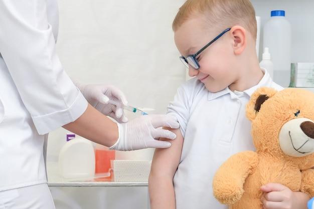 병원에서 예방 접종을 받는 어린 소년을 닫습니다. 바이러스 예방