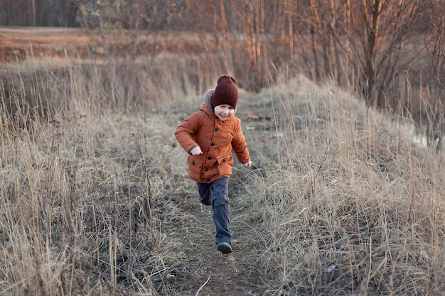 Little boy in a red jacket held out his hand, autumn field with dry grass