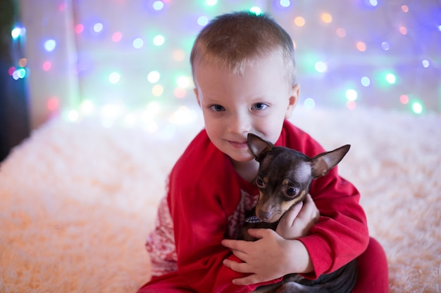 Little boy in red pajamas playing with a dog on christmas eve