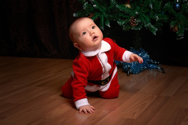 A little boy in a red santa suit near the christmas tree