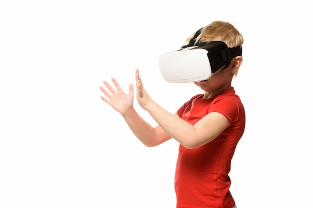 Little boy in a red shirt is experiencing virtual reality holding hands in front of him. isolate on white