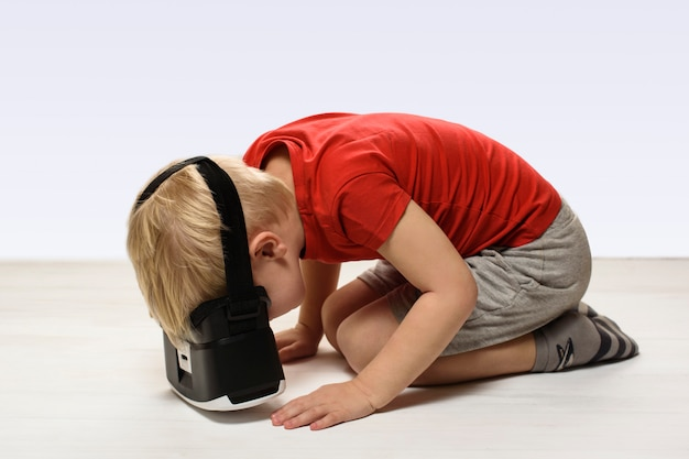 Little boy in a red shirt is experiencing virtual reality sitting on the floor.