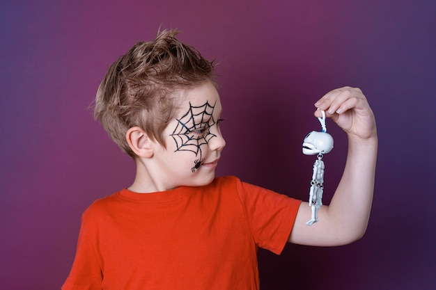 Little boy in red t-shirt holds skeleton and looks at it on purple background. halloween makeup.