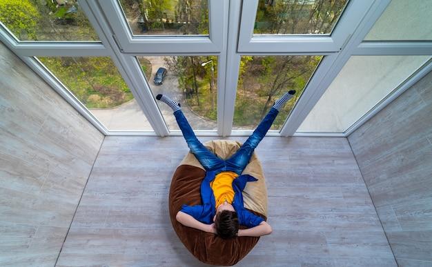 Маленький мальчик отдыхает на террасе. подросток мечтает о летнем отдыхе, глядя через стеклянную стену. дремать на мягком стуле.