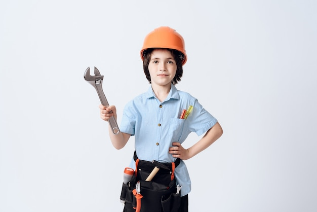 A little boy in repairman form and helmet.