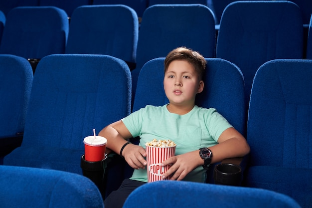 Little boy resting and enjoying action movie in cinema