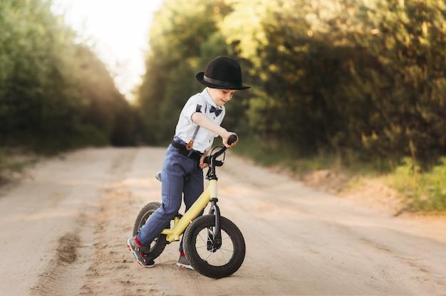 小さな男の子は自然の中で夏にバランスバイクに乗ります。ペダルなしで自転車を走らせる