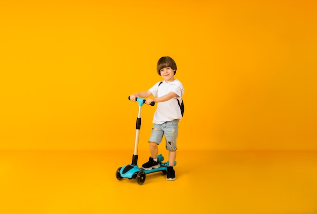 Little boy rides a scooter on a yellow surface with a place for text