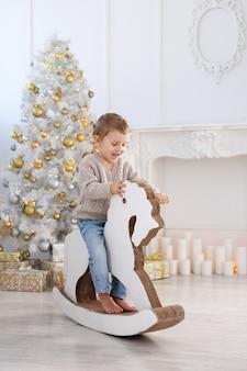 Маленький мальчик катается на картонной лошади возле елки